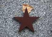 Постер, плакат: Red star and autumn birch leaf at the Soviet War Memorial with graves of Soviet soldiers fallen in t