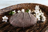 stock photo of acupressure  - Acupuncture needles on wooden plate with pebble and flowering branch - JPG