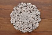 stock photo of doilies  - Colorful and crisp image of lace doily on dark wood - JPG