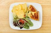 foto of crisps  - Quiche salad and potato crisps on a plate on a wooden board - JPG