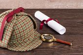 image of private investigator  - Wrapped paper sheets and magnifying glass on Old Wooden table - JPG