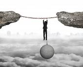 picture of ball chain  - Businessman shackled by heavy concrete ball hanging on iron chains connected two cliffs with cloudy cityscape background - JPG