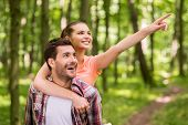 pic of walking away  - Happy young loving couple walking in park while woman hugging man and pointing away with smile - JPG