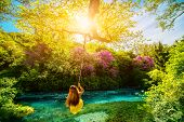 image of sulky  - Happy young woman swinging with bungee above the river in the forest - JPG