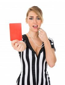 stock photo of umpire  - Young Female Referee Holding Red Card Over White Background - JPG