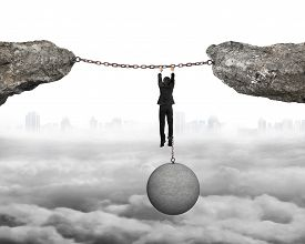 pic of shackles  - Businessman shackled by heavy concrete ball hanging on iron chains connected two cliffs with cloudy cityscape background - JPG