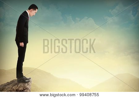 Young Business Man Looking Down The Cliff