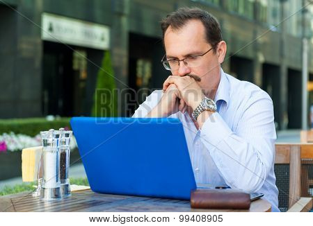 Middle age sad businessman works on laptop in outdoor cafe