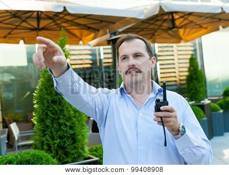 Security guard with walkie-talkie on the street