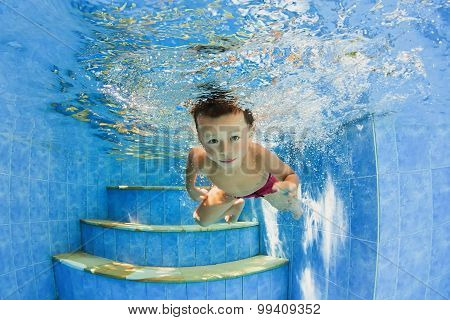 Little Smiling Child Swimming Underwater In Pool