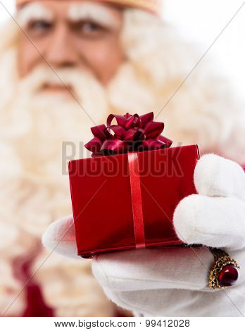 friendly Santa Claus with small gift  .Selective focus on hand with gift