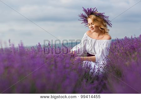 Bride in wedding dress in a field of flowering lavender.