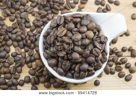 Coffee Beans In A Coffee Cup On A Wooden Table Covered With Coffee Beans.