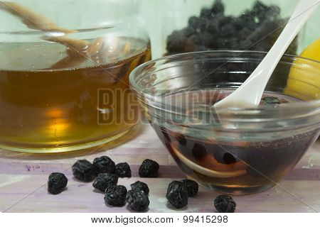 Aronia And Honey In  A Glass Dish Next To A Jar With Honey