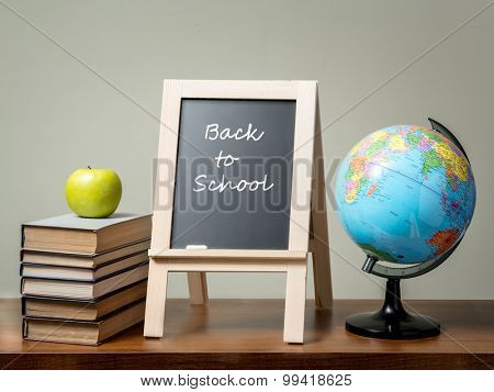 Pile of books with green apple, globe and blackboard with Back to School phrase all placed on brown desk over green wall