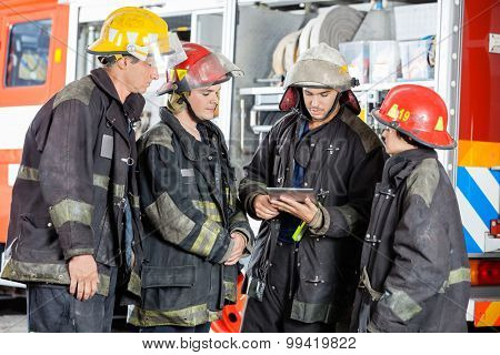 Young and mature firefighters using tablet computer against firetruck at station