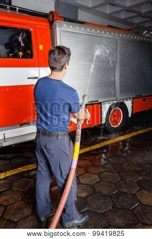 Rear view of young fireman spraying water on truck during practice at fire station