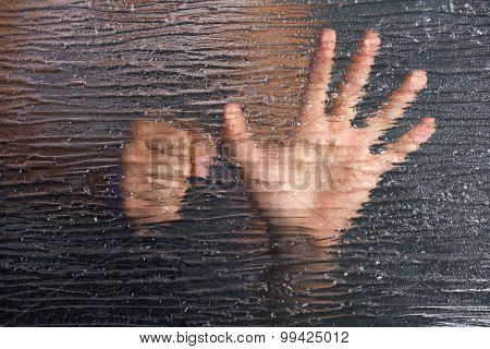 Male hand behind frosted glass, close-up