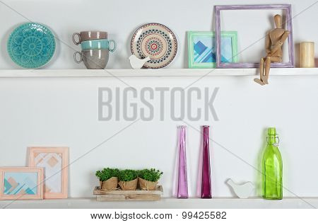 Wooden shelves with decorative things in room