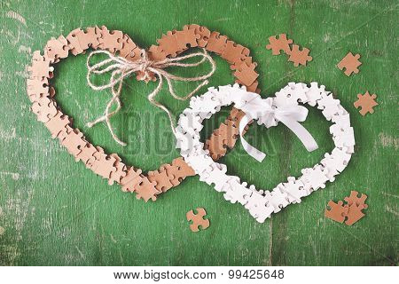 Puzzle made hearts shape on color wooden background