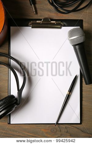Music recording scene with classical guitar, headphones, microphone and memo pad on wooden table, closeup