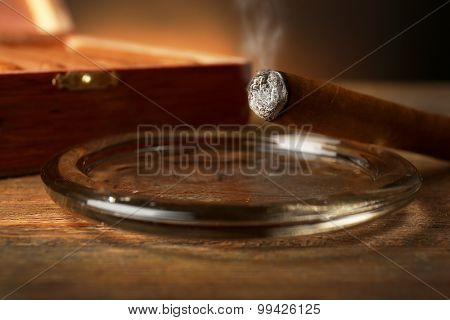 Burning cigar in ashtray on wooden table, closeup