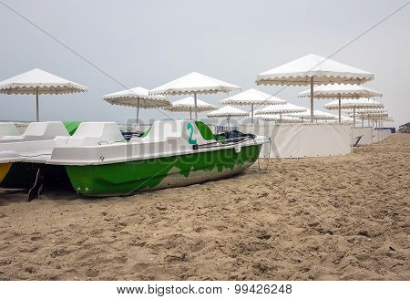 Green Catamaran On A Background Of Parasols On The Coast