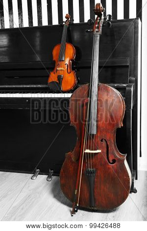 Cello and violin on piano background