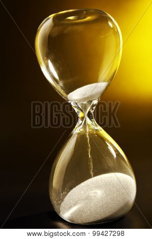 Hourglass on dark yellow background