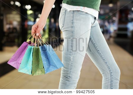 Female hand with shopping paper bags in market