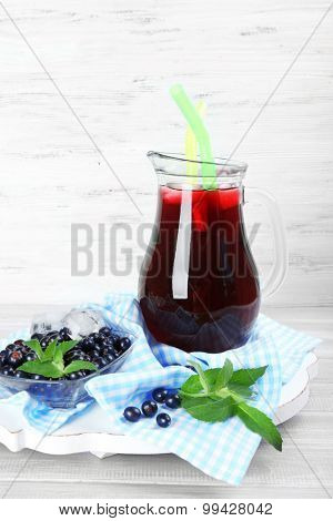 Glass jug of fresh blackcurrant juice on checkered napkin on wooden background