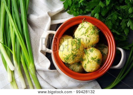 Boiled potatoes with dill in pan on table close up