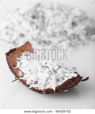 Coconut shavings in coconut shell on white background