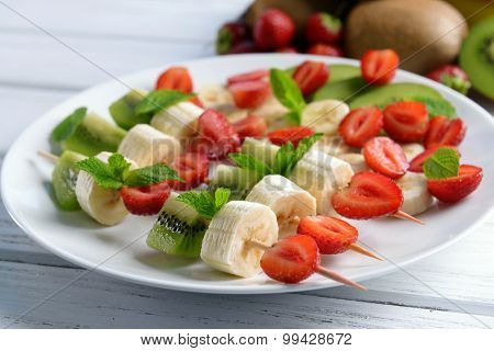 Fresh fruits on skewers in plate on wooden table, closeup