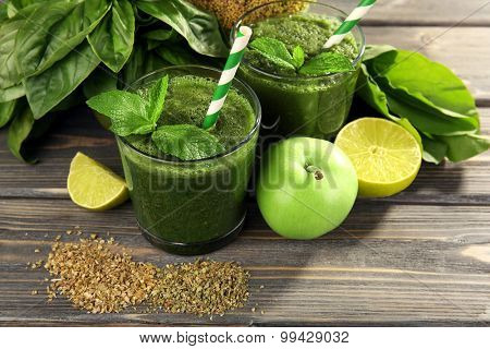 Green healthy juice with fruits and vegetables on wooden table close up