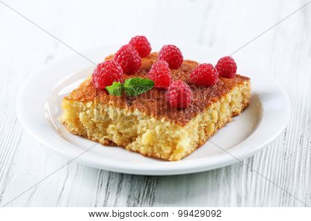 Fresh pie with raspberry in white plate on wooden table, closeup