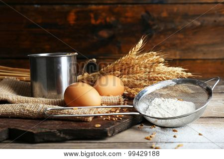 Flour and wheat on wooden table, closeup