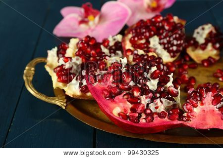 Pomegranate seeds on metal tray on wooden table, closeup