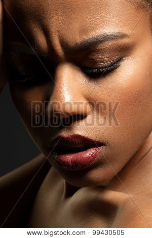 Close-up Face Of A Sad Black Girl On Black Background