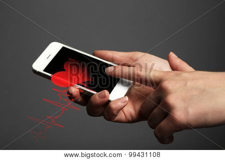 Hands holding smart mobile phone with health book app on the screen.