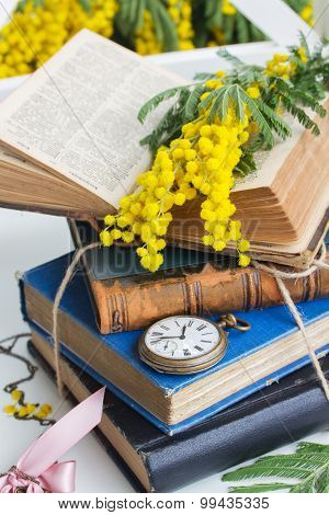 pile of old books with pocket watch