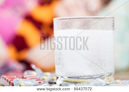 Drug Dissolves In Glass And Pill On Table Close Up