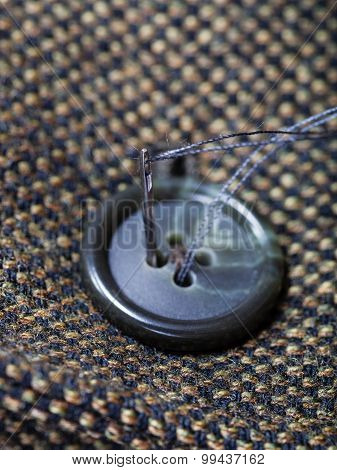 Attaching Of Button To Green Tweed By Needle