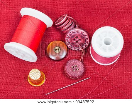 Sewing Thread, Buttons, Thimble On Red Tissue