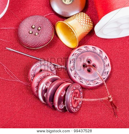Sewing Thread, Buttons, Thimble On Red Fabric