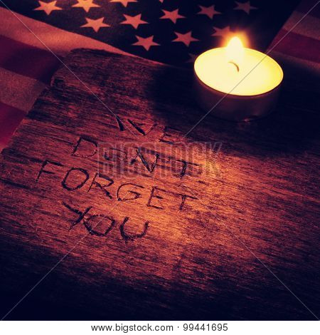 the sentence we do not forget you carved on wood and the flag of the United States and a lighted candle, with a filtered effect