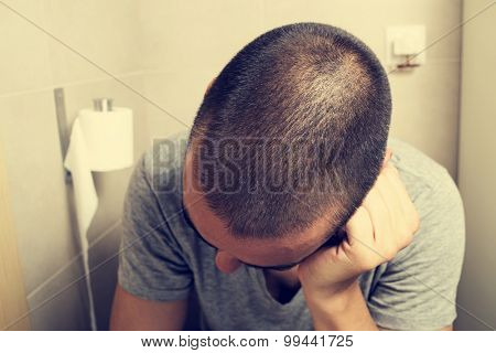 closeup of a young caucasian man in the toilet sitting in the bowl