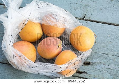 Fresh Apricots In A Transparent Plastic Bag On Old Blue-gray Wood