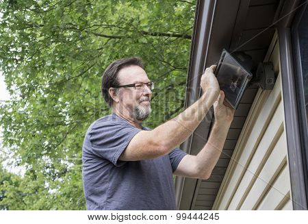 Electrician Changing Light Bulb In Exterior Light