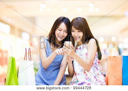 Happy Woman Looking At Smart Phone At  Shopping Mall